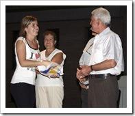 La concejala de Bienestar Social entrega un regalo a uno de los intervinientes.