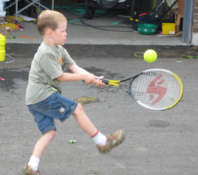 BigE with one foot up swinging the tennis racket