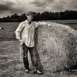 Dan Profitt down On the Farm by George Holt - People Portraits of Men ( farm, cowboy boots, cowboy hat, cowboy, sepia, hay bail, horse, hay, cloudy, musician, boots, hat )