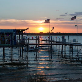 Pier and marina store backlit by a sunset on the lake by Stretch Clendennen - Landscapes Sunsets & Sunrises ( backlit, flags, peaceful, silhouette, sunset, twilight, pier, lake, marina, boat, dock,  )