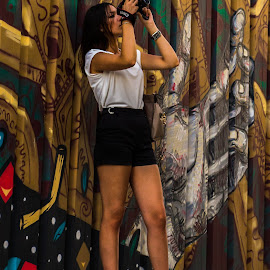 Does the girl catch the image or the image catch the girl? by Rita Brito - People Street & Candids ( woman portrait, color, graffiti, photo, street photography )
