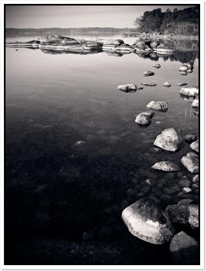 Spegelblankt hav och stenar i vatten
