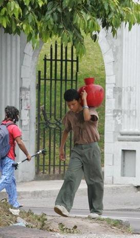 Cesar y Willian caminan para conseguir un poco de agua  cerca de la comunidad el Tanque, cerca de la Universidad de El Salvador. Foto de La Prensa, Nilton García