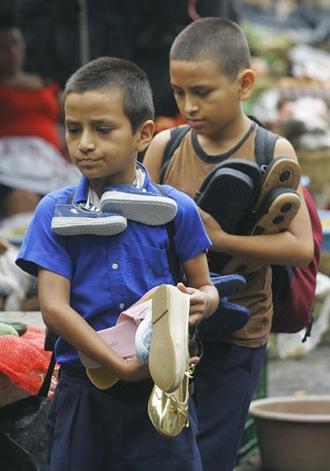 NIÑOS TRABAJADORES. Carlos Alberto, de 10, y su hermano José Manuel Rivera, de 12 años venden zapatos en La Tiendona. Afirman que un buen día venden hasta $12 dólares vendiendo unos seis pares de zapatos. Foto de La Prensa, Oscar Leiva