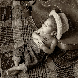 Newborn Cowboy by George Holt - Babies & Children Child Portraits ( sepia, cowboy, black and white, infant, male, sadle, cute, boy, newborn, hat )