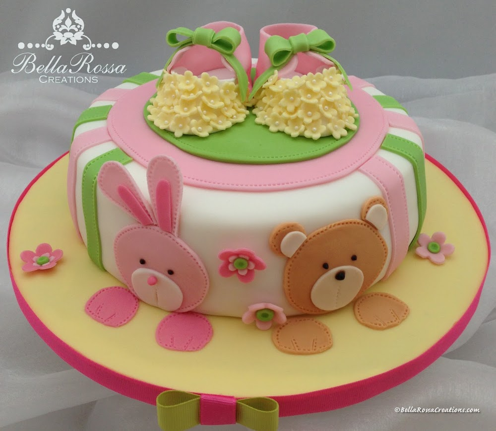 Vanilla sponge cake with caramel ganache for a Baby Shower. This cake was decorated with a 2D bunny and teddy in gum paste, lovely 3D handcrafted flower embellished booties and with a bow on top.