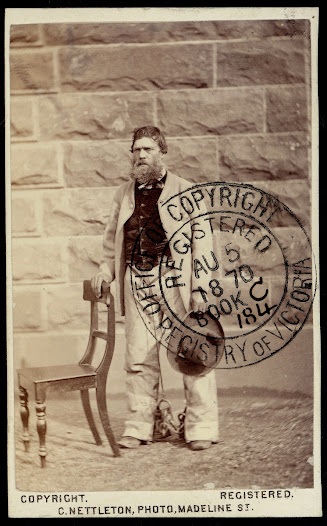 Bushranger, Harry Power, standing in front of a brick wall at Pentridge prison, ankles chained.
