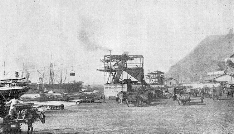 Esplendida vista de las maquinas trabajando y los medios de transporte utilizados habitualmente, carros, para llevar el carbón hasta los almacenes generales. De la Memoria del Puerto de Barcelona. Año 1.905.jpg