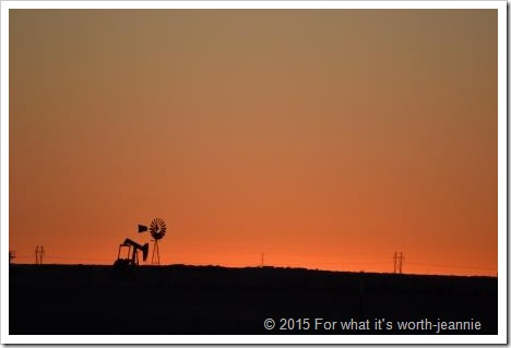 Texas cloudless sunset w oil well and windmill