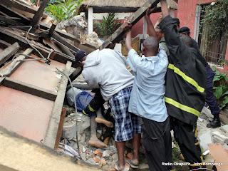 Le public, les policiers et quelques volontaires tentent de secourir une maison écroulée  ce 26 avril 2011, après la pluie qui s'est abattu la nuit à Kinshasa.  Radio Okapi/ Ph. John Bompengo