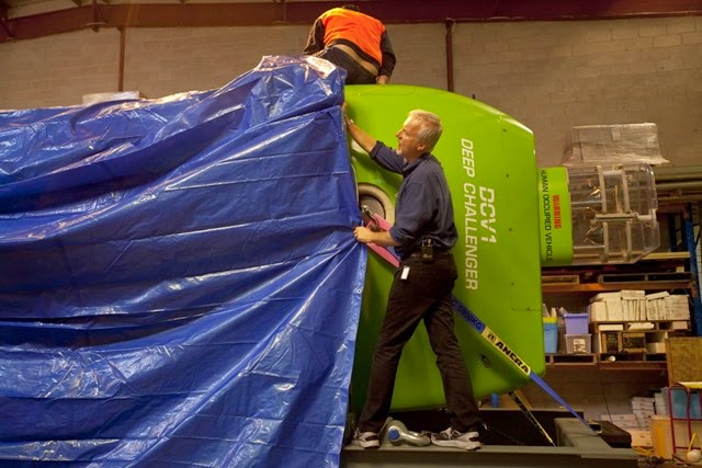 James Cameron pulling a tarp off the submersible at the Acheron Project offices in Sydney Australia