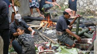 Los tubos llenos de cerdo se van colocando a la llama para empezar a cocerse.