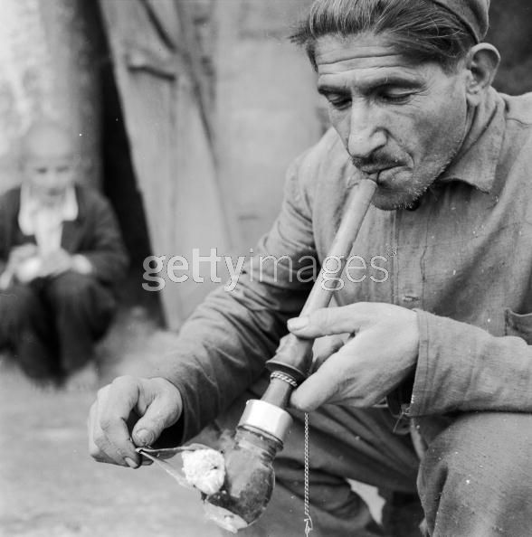 Opium Smoker circa 1950, An Iranian smoking an opium pipe. The pill of drug is heated with glowing coals and the resultant fumes inhaled with quick short puffs. (Photo by Three Lions:Getty Images).jpg