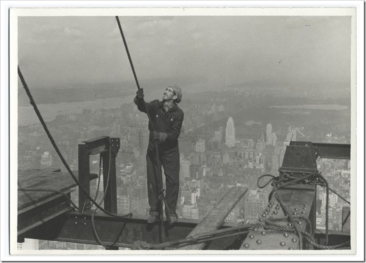 Construction-worker-standing-on-an-I-beam-pulling-a-rope-1931