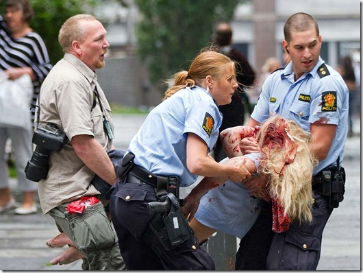 A young victim is helped in the centre of Oslo, Friday July 22, 2010, following an explosion that tore open several buildings including the prime minister's office, shattering windows and covering the street with documents.(AP Photo/Winje √jijord, Scanpix Norway) NORWAY OUT: