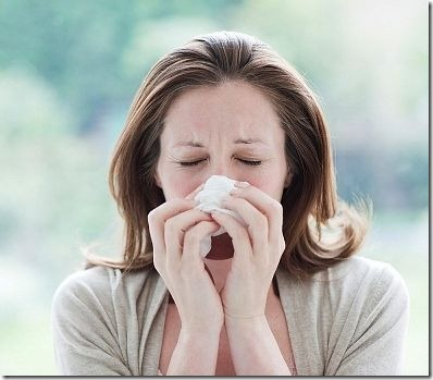 woman rubbing nose with hanky