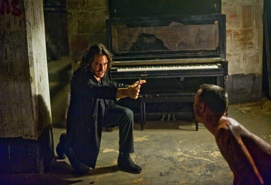 Mendoza (EDGAR RAMIREZ) holds off a possessed Jimmy (CHRIS COY) with the power of the crucifix, prayer and holy water in Screen Gems' DELIVER US FROM EVIL.