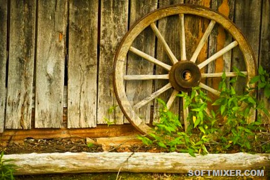 3353114-antique-wagon-wheel-leaning-against-an-antique-wooden-barn-with-weeds-growing-in-front