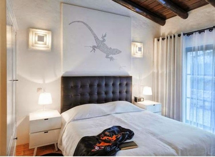 decorating-white-bedroom-with-black-tufted-headboard-and-wall-sconces-and-animal-wall-art-700x510