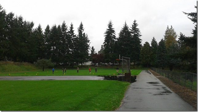 Playing flag football in a rain soaked park