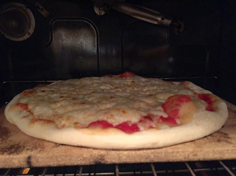Image of pizza in the oven while being baked