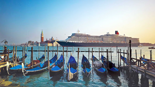 Queen Elizabeth glides past St. Mark's Square in Venice, one of the memorable destinations aboard a Cunard cruise.