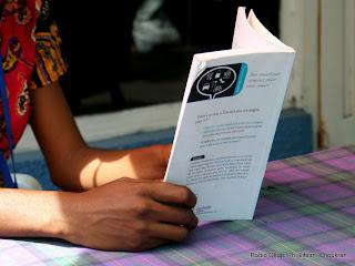 Des mains d'une lectrice tenant un livre. Radio Okapi