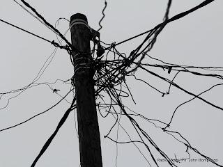 Des câbles électriques de la SNEL raccordés sur un poteau en bois, dans un quartier populaire de Kinshasa. Radio Okapi/ Ph. John Bompengo