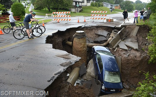 A car sits in a giant sinkhole in Duluth, Minn. Wednesday, June 20, 2011. Residents evacuated their homes and animals escaped from pens at a zoo as floods fed by a steady torrential downpour struck northeastern Minnesota, inundating the city of Duluth, officials said Wednesday. (AP Photo/The Star Tribune, Brian Peterson)  MANDATORY CREDIT; ST. PAUL PIONEER PRESS OUT; MAGS OUT; TWIN CITIES TV OUT