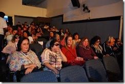 Platéia do teatro; alguns espectadores usam fones de ouvido para acompanharem a audiodescrição da peça