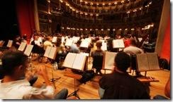 Festival de Ópera: orquestra tocando; músicos lêeem as partituras