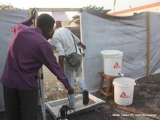 De gauche à droite, un préposé de MSF désinfecte, un homme sortant du centre de prise en charge des victimes de l'épidémie du choléra à Kinshasa. Radio Okapi/ Ph. John Bompengo