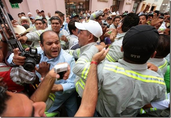 VERACRUZ, VERACRUZ., 01MAYO2014.- Trabajadores de la empresa de tubos Tenaris - Tamsa agredieron a periodistas, dañaron equipo de fotógrafos y ultrajaron sexualmente a reporteras cuando intentaban entrevistar al dirigente del sindicato, Pascual Lagunes Ochoa durante el desfile del Día del Trabajo en el puerto de Veracruz. <br>FOTO: FÉLIX MÁRQUEZ /CUARTOSCURO.COM