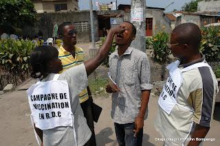 En avant plan, de gauche à droite une femme vaccinateur entrain d'administrer le vaccin contre la polio à un passant sur une des avenues principale de Kinshasa ce 23 mars 2011, lors de la campagne anti polio en RDC. Okapi Okapi / Ph John Bompengo