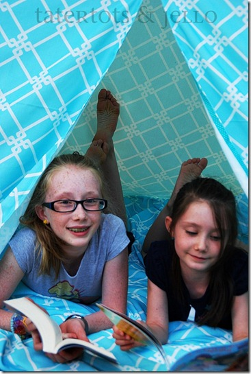 hannah and ella reading in the teepee