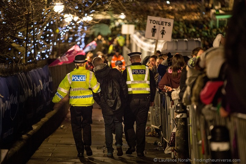 police escort drunken reveller away from hogmany new years edinburgh