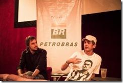 Duas pessoas em uma mesa, atrás dela vê-se o logotipo da Petrobras