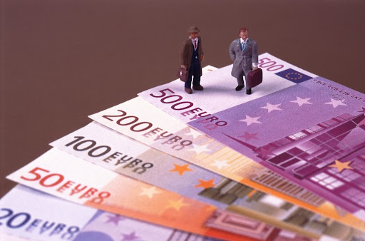 businessman standing on euro-notes