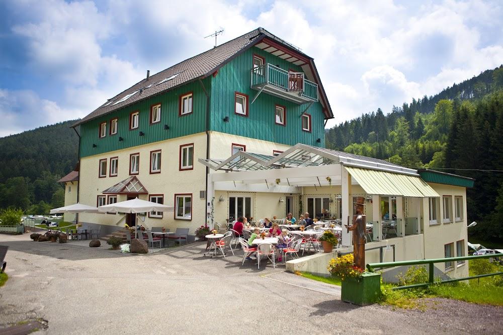 Du siehst das Familienrestaurant des Kleinenzhofes, ein türkisfarbenes Haus.