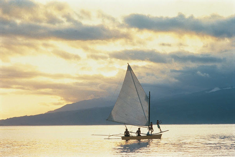 At the end of a beautiful day, enjoy the view of sailboats at sunset on Tahiti.