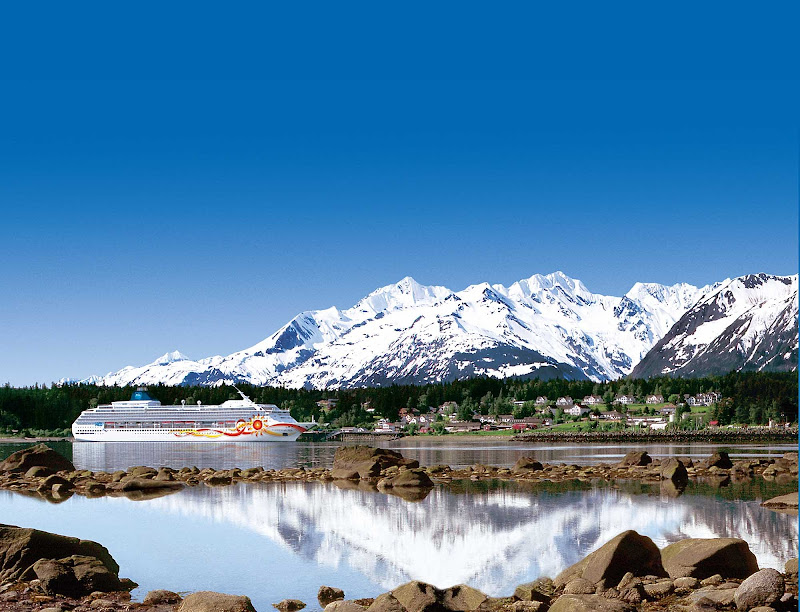 Norwegian Sun cruises along the Alaska coastline with a backdrop of snowcapped peaks and emerald green trees.