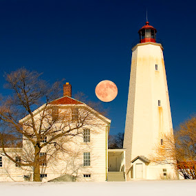Sandy Hook Light with Moon by Bill Morris - Buildings & Architecture Public & Historical ( moon, blue sky, snow, light house, trees )