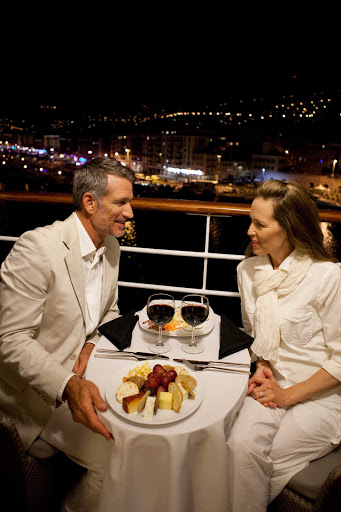 Azamara-Quest-balcony-dining-Nice-France - Enjoy a romantic dinner for two accompanied by the glittering lights of Nice, France, on an Azamara cruise.