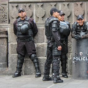 by Judith Dueck - People Group/Corporate ( independence square, america, protective, cap, cop, street, protest, state, stability, riot, helmet, officer, police, gear, relaxed, knee pads, government, crowd, armed, vest, baton, quito, unstable, control, unrest, presidential palace, ecuador, uniform, bullet-proof, heavy, demonstration, country, south, force, badge, shield, wall, banks )