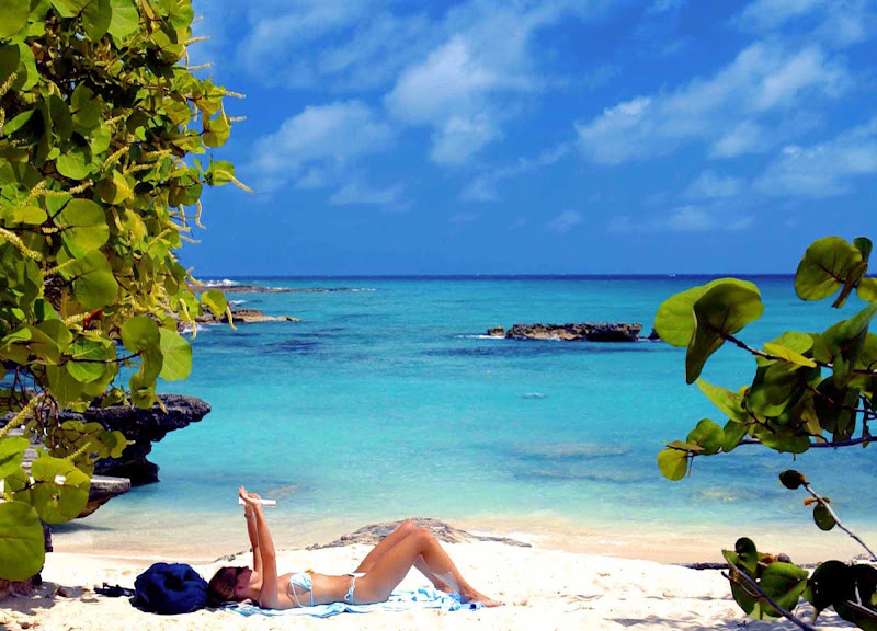 A woman reads while sunbathing along the azure shoreline of Smith Cove on Grand Cayman Island.