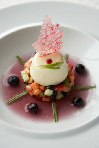 Blu_Pannacotta - Blu restaruant's creamy Pannacotta served on a fresh fruit salad with a berry compote is one of the artfully presented desserts served on your Celebrity cruise.