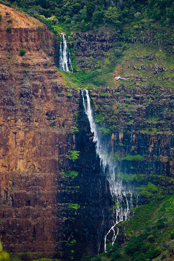 Waimea-Canyon-waterfall - A waterfall in Waimea Canyon, known as the Grand Canyon of the Pacific, on the western side of Kauai viewed from a helicopter.