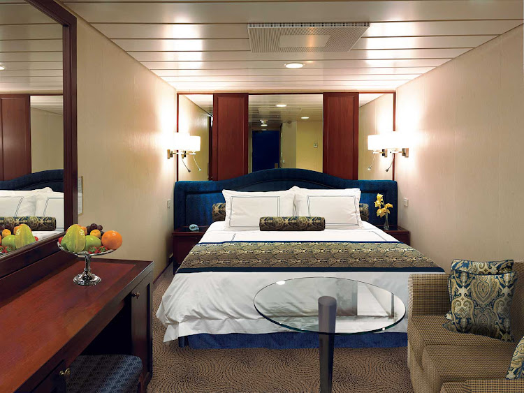Inside staterooms on Oceania Insignia contain a queen bed with 1,000-thread-count linens, seating area, vanity desk, refrigerated mini-bar, breakfast table, Bulgari amenities, flat-screen TV with live satellite and twice-daily maid service.