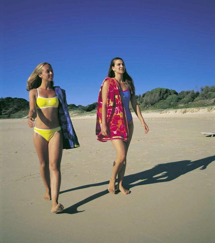 Two women stroll along the beach at Hat Head, near South West Rocks, Kempsey, North Coast NSW, Australia.
