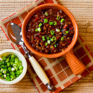 Vegan Lentil Chili with Roasted Red Peppers, Olives, and Green Onion.